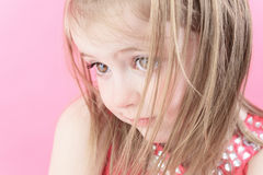 En ledsen liten dockaflicka i rosa bakgrund Arkivbild
