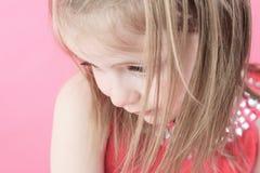 En ledsen liten dockaflicka i rosa bakgrund Royaltyfria Bilder