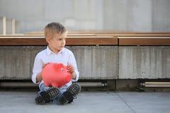 En ledsen pojke som rymmer en röd moneybox och resväska Royaltyfri Fotografi