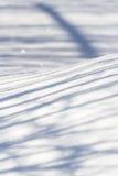 En lek av skuggor på snö Arkivfoto