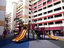 En lekplats i mitt av två HDB-byggnader i staden av Tampines, Singapore Fotografering för Bildbyråer