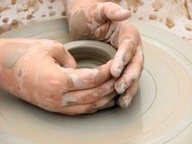 En lerakruka på ett krukmakerihjul med framställning det räcker Arkivfoton