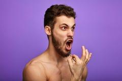 En lida man som ut plockar hans skägghår som står isolerat över blå bakgrund, royaltyfri foto