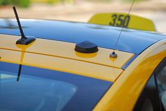 The roof of a yellow taxi cab showing the antennas of the communications equipment inside. royalty free stock photography