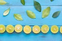 en limefruktcitron är det halva snittet och ordnar till kolonnen på blått träb Royaltyfria Foton