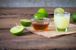 en limefruktcitron med fruktsaft och honung i genomskinligt exponeringsglas med säcken Royaltyfri Fotografi