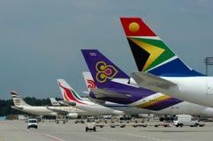 En lineup av färgrika flygplansvansar arkivfoto