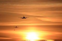 En lineup av flygplan som ankommer på solnedgången royaltyfri foto