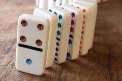 En linje av dominobrickor på trä royaltyfria foton