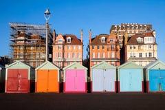 En linje av 7 mångfärgade strandkojor på Brighton promenad i t Royaltyfri Foto