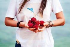 En litchiplommonfrukt i händerna av en flicka i armband Fotografering för Bildbyråer