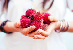 En litchiplommonfrukt i händerna av en flicka i armband Royaltyfria Bilder