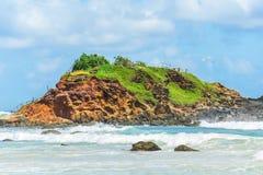 En liten ö bland vågorna Arkivfoto