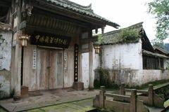 En liten bro hänger över en kanal framme av en tempel i Shangli (Kina) Arkivbild