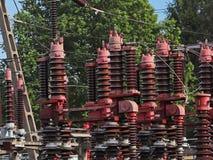 En liten elektrisk transformatorstation i den öppna luften Keramiska isolatorer och trådar för hög spänning den isolerade tecknad royaltyfri fotografi