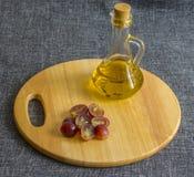 En liten exponeringsglastillbringare med olja, högg av druvor På en träskärbräda royaltyfri bild