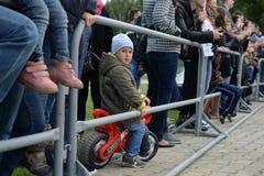 En liten fan på en röd motorcykel Royaltyfria Foton
