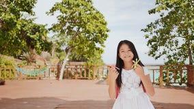 En liten filippinsk skolflicka visar snurrspinnare tropisk liggande Sommar Barndom lager videofilmer
