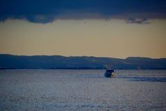 En liten fiskebåt på solnedgången; stillsam seascape med underbart guld- ljus och tyst havsvatten royaltyfri fotografi