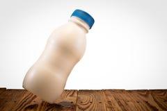 En liten flaska av mjölkar på den wood tabellen Royaltyfri Fotografi