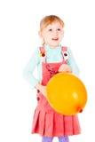 En liten flicka i en klänning som leker med en ballong royaltyfri foto