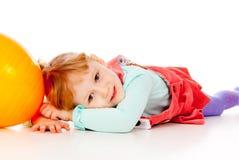 En liten flicka i en klänning som leker med en ballong arkivbild