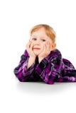 En liten flicka i en klänning som ser från sidan som är tänkande royaltyfri fotografi