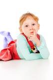 En liten flicka i en röd klänning, liggande posera royaltyfri bild