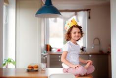 En liten flicka med en pappers- krona hemma och att se kameran arkivfoto
