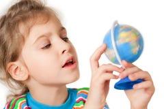 En liten flicka ser jordklotet Arkivfoton