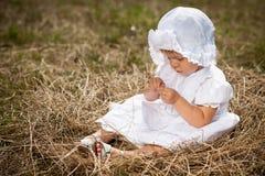 En liten flicka sitter i bygga bo Royaltyfri Fotografi