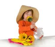 En liten flicka som ordnar blommor på bordlägga Arkivfoto