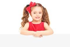 En liten flicka som poserar bak en panel Arkivbild