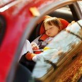 En liten flicka sover i bil royaltyfri fotografi