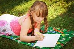 En liten flicka tecknar Arkivbild