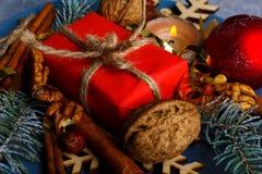 En liten gåvaask bredvid en brinnande stearinljus, valnötter och kanelbruna pinnar Närbild white för juldekorisolering Arkivfoto