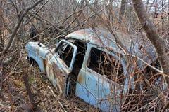 En liten gammal blå bil som överges i skogen under vintermånaderna royaltyfri bild