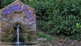 En liten gammal stenstruktur som vatten häller från arkivfoto