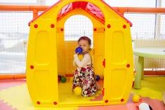En liten gladlynt flicka sitter i ett plast- leksakhus för barn och rymmer flera färgrika bollar i hennes händer En gul kulör hou arkivbilder