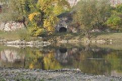 En liten grotta på banken av floden Fotografering för Bildbyråer