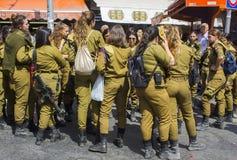 En liten grupp av av - skrattar pratar kvinnliga Israels försvarsmaktvärnpliktige för arbetsuppgift med en beväpnad vakt och till royaltyfri fotografi