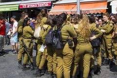 En liten grupp av av - skrattar pratar kvinnliga Israels försvarsmaktvärnpliktige för arbetsuppgift med en beväpnad vakt och till royaltyfria foton