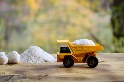 En liten gul leksaklastbil laddas med en sten av vit som är salt bredvid en hög av salt En bil på en träyttersida mot en backgro Arkivbild