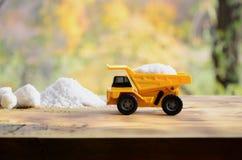 En liten gul leksaklastbil laddas med en sten av vit som är salt bredvid en hög av salt En bil på en träyttersida mot en backgro Arkivfoto