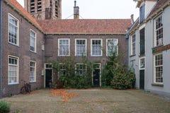 En liten härlig borggård med historiska hus i delftfajans, Nederländerna arkivfoto
