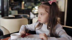 En liten härlig flicka äter på ett kafé och dricker med doftande te stock video