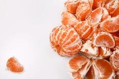 En liten hög av den ljusa apelsinen skalade mandariner på en vit bakgrund, till den vänstra en lobulen av frukt, i mitt en tom sp Royaltyfri Fotografi