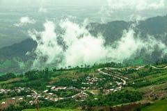 En liten by i dalen med ljus dimma royaltyfria bilder