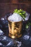 En liten järnhink står på en tabell med is Arkivfoto