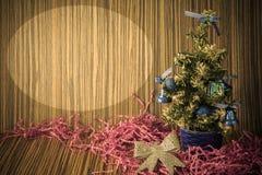 En liten julgran på en träbakgrund för vykort och Arkivfoto